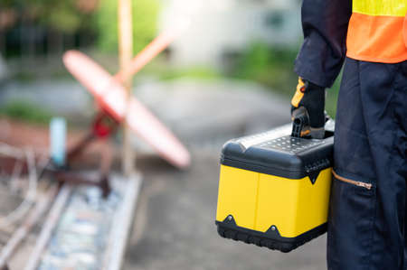 Male maintenance worker hand carrying yellow work tool box at construction site. Equipment for mechanical or civil engineering project Stok Fotoğraf