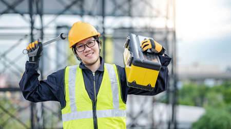 Male Asian mechanic or maintenance worker man wearing protective helmet and reflective vest carrying work tool box and wrench at construction site. Equipment for mechanical engineering project Stok Fotoğraf