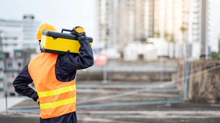 Asian maintenance worker man wearing protective suit and safety helmet carrying work tool box at construction site. Equipment for civil engineering project