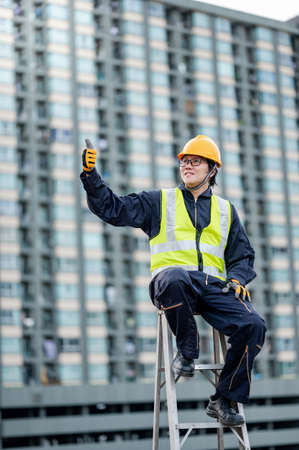 Asian maintenance worker man with safety helmet and green vest showing thumb up sitting on aluminium step ladder at construction site. Civil engineering, Architecture and building service concepts Stok Fotoğraf