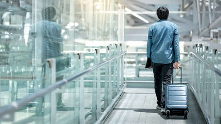 Asian man tourist carrying suitcase luggage and digital tablet walking on walkway in airport terminal gate hall. Travel insurance concept