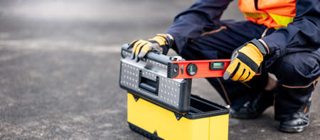 Male mechanic or maintenance worker man holding red aluminium spirit level tool or bubble levels opening tool box at construction site. Equipment for civil engineering project