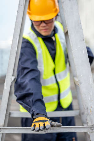 Asian maintenance worker man with safety helmet and reflective suit adjusting aluminium step ladder at construction site. Civil engineering, Architecture builder and building service concepts Stok Fotoğraf