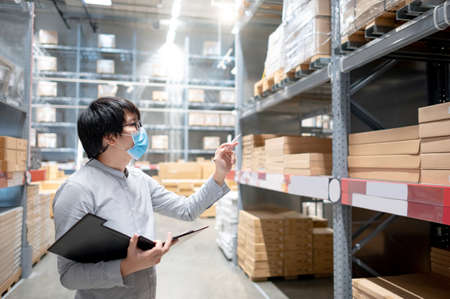 Asian man worker wearing face mask doing stocktaking of product in cardboard box on rack in warehouse by using clipboard. Physical inventory count and preventing the spread of COVID-19 (Coronavirus). Banque d'images