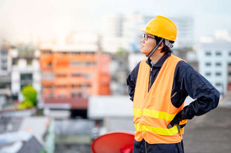 Asian maintenance worker man wearing reflective suit and safety helmet working at construction site. Civil engineering, Architecture builder and building service concepts Stok Fotoğraf
