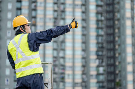 Asian maintenance worker man with safety helmet and green vest showing thumb up standing on aluminium step ladder at construction site. Civil engineering, Architecture and building service concepts