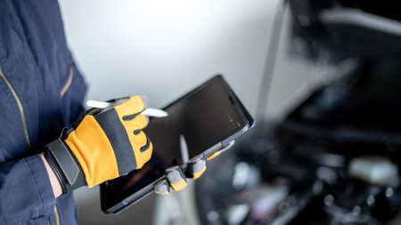 Male auto mechanic with protective suit using digital tablet for checking car in auto service garage. Mechanical maintenance engineer working in automotive industry. Automobile servicing and repair Foto de archivo