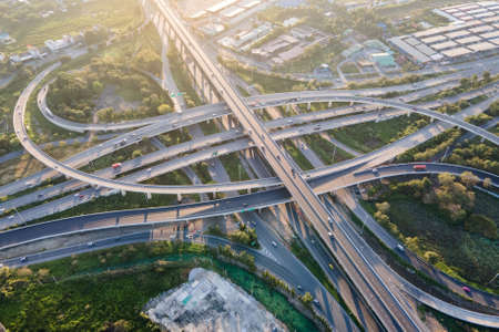 Aerial view of road interchange or highway intersection with busy urban traffic speeding on the road. Junction network of transportation taken by drone. Banque d'images