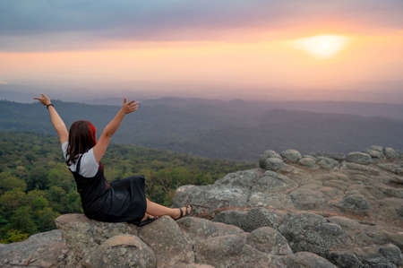 Achievement concept. Asian woman raising hands sitting on Nodule rock field called Lan Hin Pum enjoy looking at sunset over scenic landscape of Phu Hin Rong Kla National Park in Phitsanulok, Thailand.