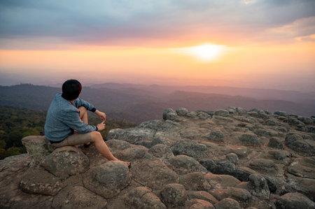 Achievement concept. Asian man raising hands sitting on Nodule rock field called Lan Hin Pum enjoy looking at sunset over scenic landscape of Phu Hin Rong Kla National Park in Phitsanulok, Thailand.