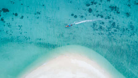 Stunning summer landscape. Aerial view of fishing long tail boat in turquoise Andaman sea near beautiful white beach at Koh Lipe or Lipe island, Satun, Southern Thailand. Shot from drone Zdjęcie Seryjne