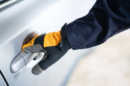 Male auto mechanic hand wearing protective glove holding car door handle in auto service garage. Mechanical maintenance engineer working in automotive industry. Automobile servicing and repair Zdjęcie Seryjne