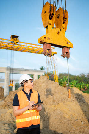 Smart Asian worker man or male civil engineer with protective safety helmet and reflective vest using digital tablet for project planning and checking crane lifting hook at construction site. Zdjęcie Seryjne