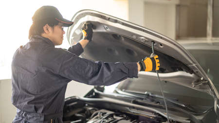 Asian auto mechanic opening bonnet hood checking car engine in auto service garage. Mechanical maintenance engineer working in automotive industry. Automobile servicing and repair