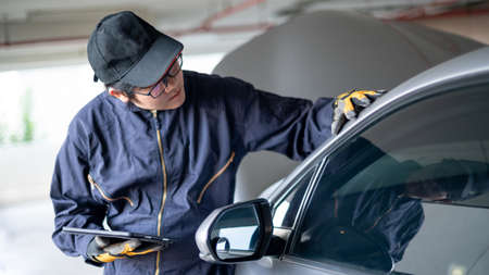 Asian auto mechanic holding digital tablet checking car in garage. Mechanical maintenance engineer working in automotive industry. Automobile servicing and repair concept
