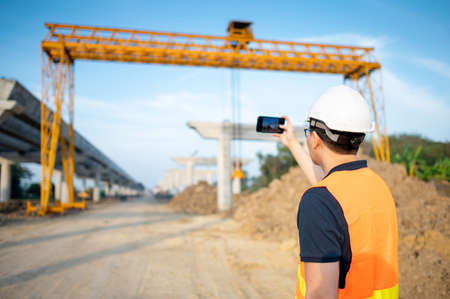 Smart Asian worker man or male civil engineer with protective safety helmet and reflective vest using using smartphone for taking photo at construction site. Zdjęcie Seryjne