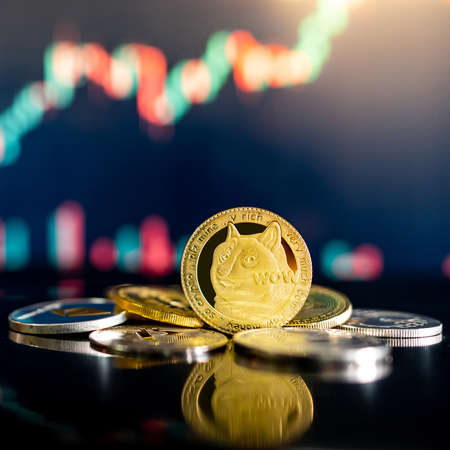 Gold Dogecoin and other crypto coins on reflecting table. Blurred candlestick chart in the background. DOGE is the most popular meme coin in cryptocurrency world.