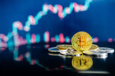 Bitcoin and other crypto coins on reflecting table. Blurred candlestick chart in the background. BTC known as digital gold asset in cryptocurrency world.