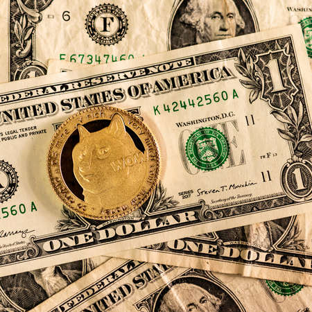 Gold Dogecoin on one dollar banknotes. DOGE road to 1 dollar. The  most popular meme crypto coin in cryptocurrency world. Zdjęcie Seryjne