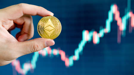 Hand holding gold ETH coin with blurred candlestick chart in the background. Ethereum is a decentralized, open-source blockchain with smart contract. Cryptocurrency and decentralized finance concept
