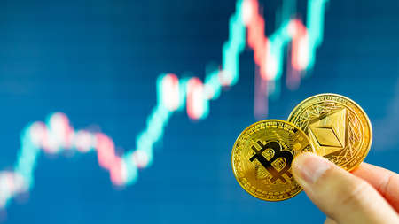 Hand holding gold Bitcoin and Ethereum with blurred candlestick chart in the background. Cryptocurrency and Decentralized finance concept