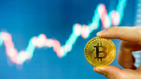 Investor hand holding gold Bitcoin with blurred candlestick chart in the background. BTC known as digital gold asset in cryptocurrency world.