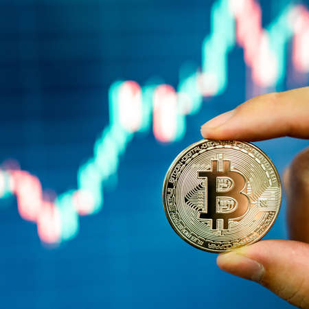 Investor hand holding silver Bitcoin with blurred candlestick chart in the background. BTC known as digital gold asset in cryptocurrency world.