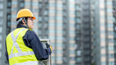 Asian maintenance worker man with safety helmet and reflective suit climbing aluminium step ladder at construction site. Civil engineering, Architecture builder and building service concepts Zdjęcie Seryjne