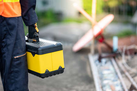 Male maintenance worker hand carrying yellow work tool box at construction site. Equipment for mechanical or civil engineering project Zdjęcie Seryjne