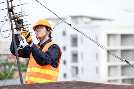 Male electrical worker or Asian man electrician wearing safety helmet and reflective suit repairing an old TV antenna and cable on rooftop of building. Zdjęcie Seryjne
