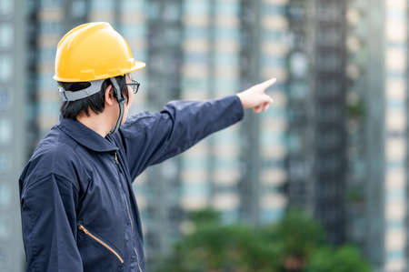 Asian maintenance worker man with safety helmet and protective suit pointing at construction site. Civil engineering, Architecture builder and building service concepts