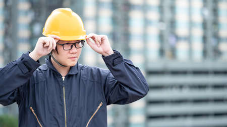 Asian maintenance worker man wearing protective suit and safety helmet working at construction site. Civil engineering, Architecture builder and building service concepts