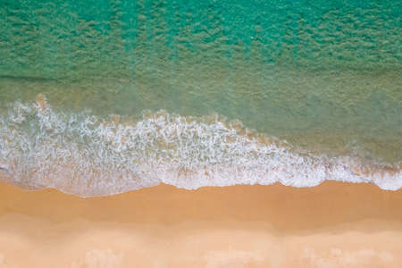 Aerial view of turquoise ocean wave reaching the coastline. Beautiful tropical beach from top view. Andaman sea in Thailand. Summer holiday vacation concept Zdjęcie Seryjne