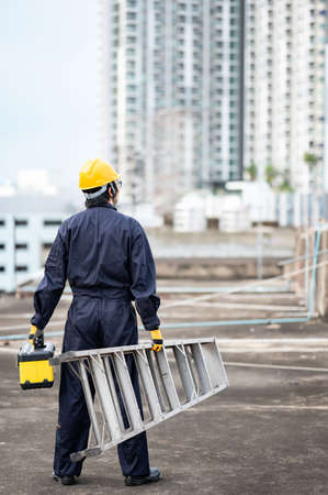 Asian maintenance worker man with protective suit and safety helmet carrying aluminium step ladder and tool box at construction site. Civil engineering, Architecture builder and building service