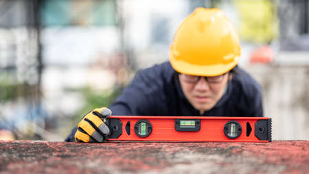 Asian maintenance worker man holding red aluminium spirit level tool or bubble levels at construction site. Equipment for civil engineering project Zdjęcie Seryjne