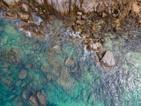 Aerial view of turquoise ocean wave reaching the coastline. Beautiful tropical coastal landscape from top view. Andaman Sea in Thailand. Summer holiday vacation concept Zdjęcie Seryjne