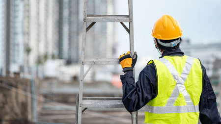 Asian maintenance worker man with safety helmet and reflective suit carrying aluminium step ladder at construction site. Civil engineering, Architecture builder and building service concepts