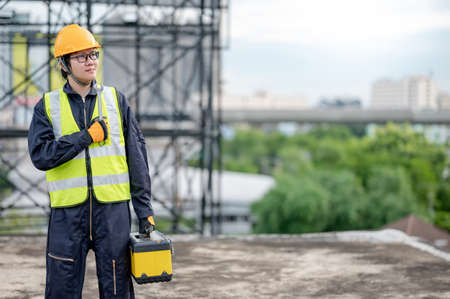 Male Asian mechanic or maintenance worker man wearing protective helmet and reflective vest carrying work tool box and wrench at construction site. Equipment for mechanical engineering project Zdjęcie Seryjne