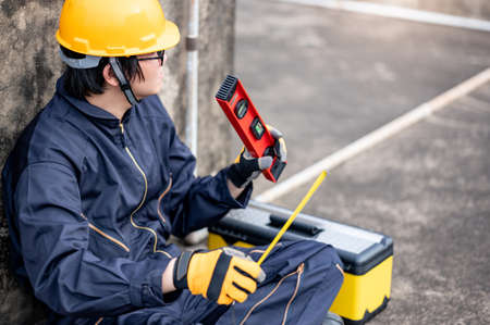 Maintenance worker man or male Asian mechanic wearing protective suit and helmet holding tape measure and level tool at construction site. Equipment for civil engineering project