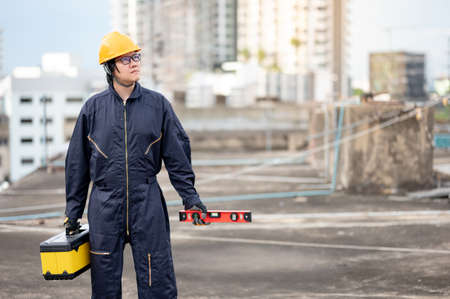 Asian maintenance worker man wearing protective suit and helmet holding red aluminium spirit level tool or bubble levels and work tool box at construction site. Equipment for civil engineering project Zdjęcie Seryjne