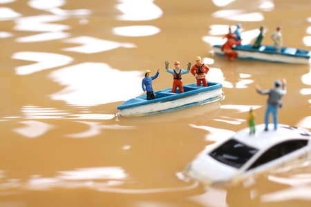 Diorama of rescuers heading to rescue by boat with people unable to evacuate because of flood damage Standard-Bild
