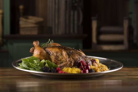 Roasted turkey chicken garnished with blackberry, red berry, cherries, and spices on a rustic table and background
