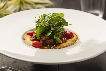 creamy polenta made with corn flour with confit tomatoes and salad with blurred background