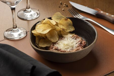 steak tartare and potato chips and parmesan on a ceramic bowl, leather table mat napkin and wine glass