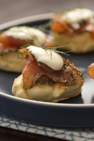 dried smoked salmon gravlax with dill and sour cream on blini pancake and blue ceramic plate and napkin on wooden table