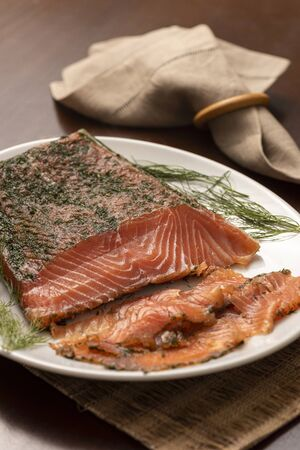 dried smoked salmon gravlax with dill on a white platter and napkin on background Stock fotó