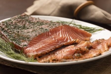 dried smoked salmon gravlax with dill on a white platter and napkin on background