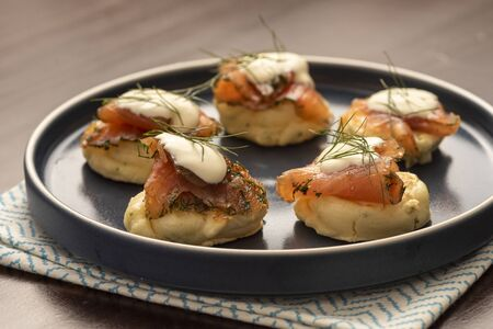 dried smoked salmon gravlax with dill and sour cream on blini pancake and blue ceramic plate and napkin on wooden table Stock fotó