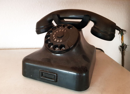 Old dusty telephone with dial Stock Photo