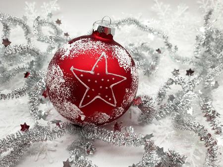 Bola de árbol de Navidad roja sobre estrella blanca. Fondo Foto de archivo